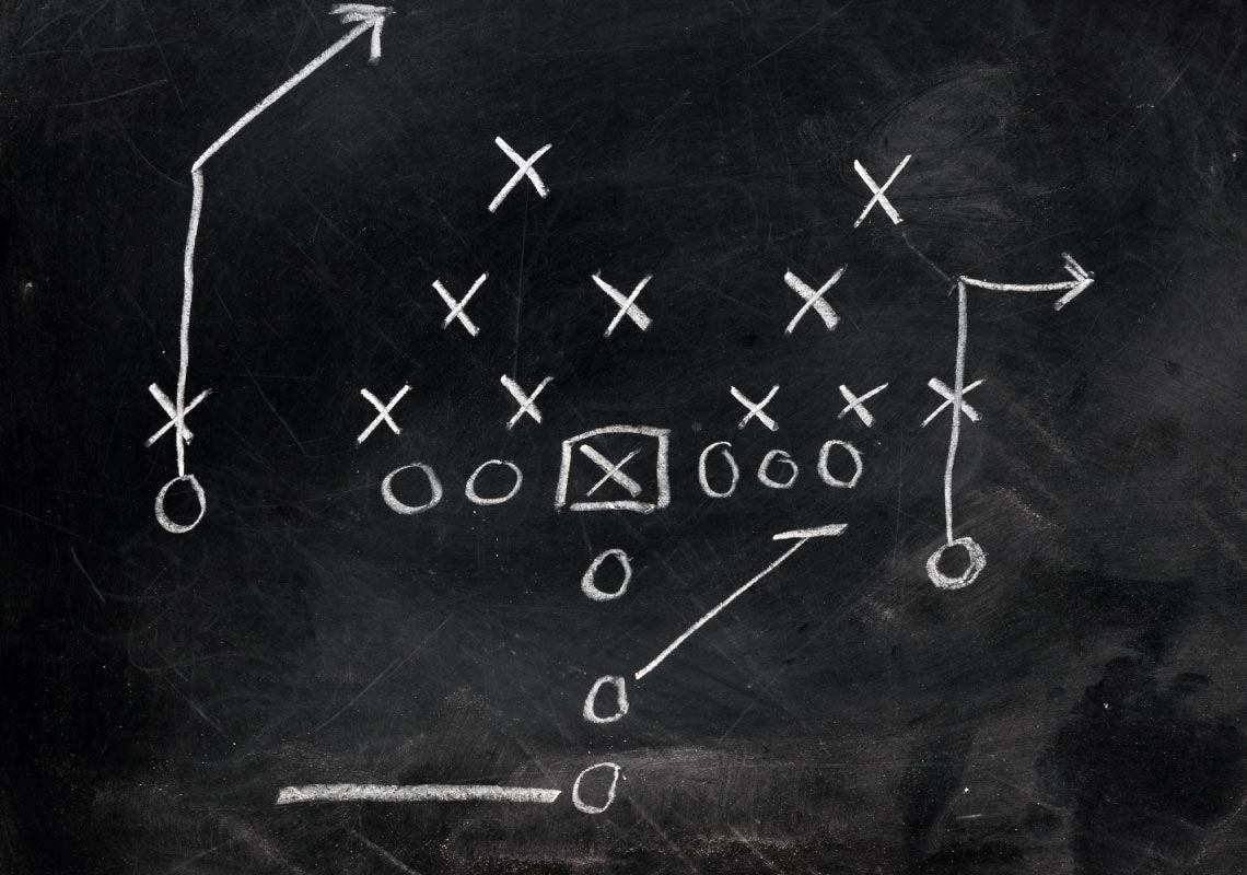 Football X's and O's on black chalkboard