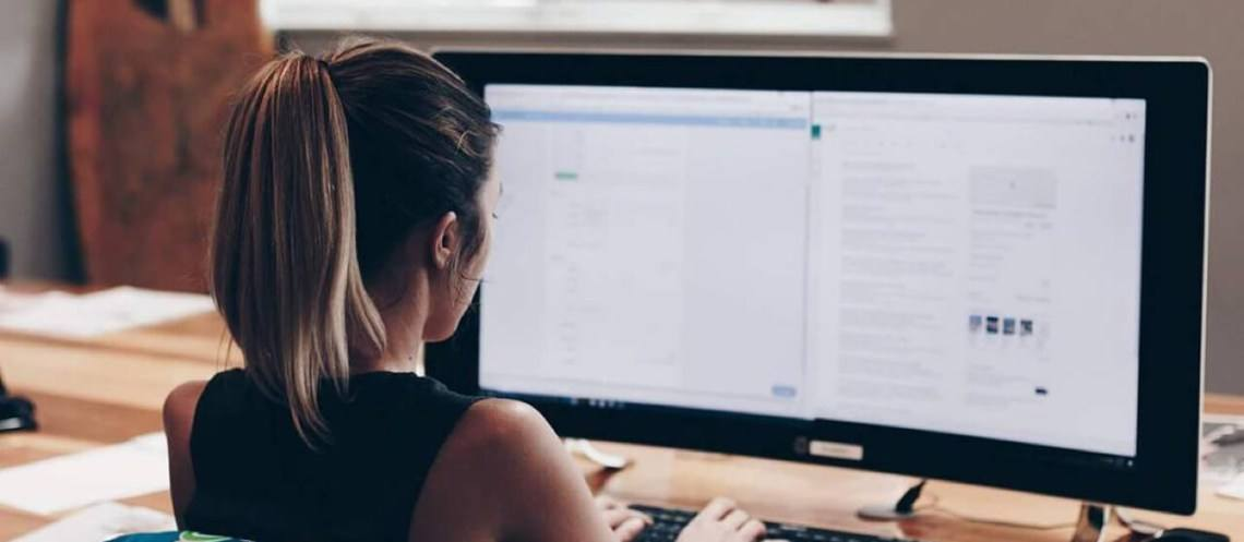 woman sitting at computer, view from behind